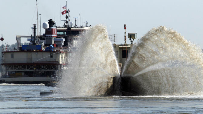 A spray of sand laced water shoots out from the Dredge Jadwin, a U.S. Army Corps of Engineers vessel that is clearing out some of the silt and left over mud and debris from last year's record flood on the Mississippi River and cutting a deeper channel for barges and their towboats to navigate north of Greenville, Miss., Wednesday, Aug. 22, 2012. Coast Guard Capt. William Drelling said Wednesday that authorities would inspect the channel near Greenville, Mississippi, then reset navigation buoys allowing barge traffic to resume on a limited basis as both federal agencies deal with the continued drought that has lowered the Mississippi River. (AP Photo/Rogelio V. Solis)