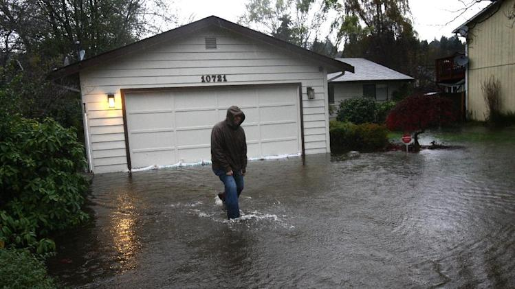 Dan Zarelli walks through a friend's flooded yard near Nathan Hale High School during a significant rainfall on Monday, Nov. 19, 2012. Water running toward Thornton Creek surrounded some homes in the neighborhood. (AP Photo/seattlepi.com, Joshua Trujillo)