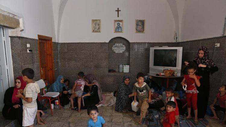 Palestinians start their day inside the St. Porphyrios Church in Gaza City, Wednesday, July 23, 2014. Entire families are sleeping on thin sheets on the hard church floors, fasting during the holy month of Ramadan. (AP Photo/Lefteris Pitarakis)