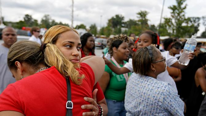 Shanique Worthey, right, is embraced by her mother Daphne Morris, while waiting to be reunited with her son five-year-old son Skyler Worthey as students from Ronald E. McNair Discovery Learning Academy are picked up by loved ones in a Walmart parking lot after they were evacuated when a gunman entered the school, Tuesday, Aug. 20, 2013, in Decatur, Ga. (AP Photo/David Goldman)