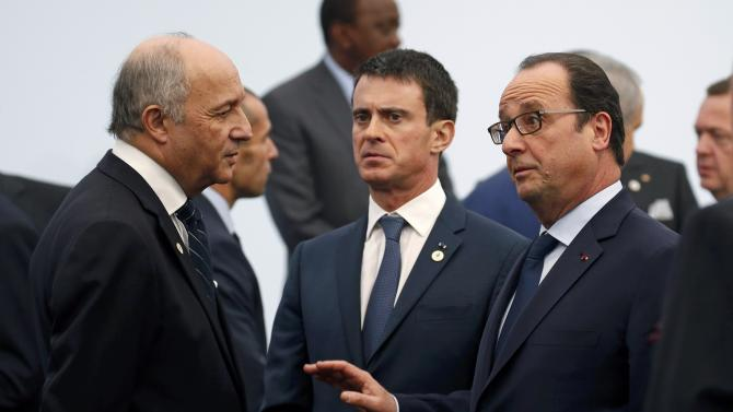 French President Francois Hollande speaks with French Foreign Affairs Laurent Fabius, President-designate of COP21, and Prime Minister Valls before a family photo during the opening day of the World Climate Change Conference 2015 in Le Bourget