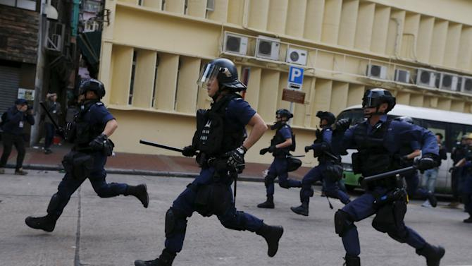 Riot police move forward to charge at protesters during a clash at Mongkok district in Hong Kong