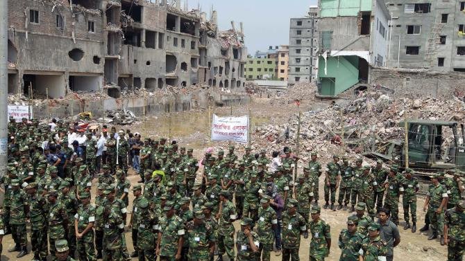 Bangladesh army soldiers and others gather at the wreckage of a Bangladeshi garment factory building to offer prayers for the souls of the 1,127 people who died in the structure's collapse last month, in Savar, near Bangladesh, Tuesday, May 14, 2013. The Islamic prayer service was held a day after the army ended the nearly three-week, painstaking search for bodies among the rubble of the worst tragedy in the history of the global garment industry and turned control of the site over to the civilian government for cleanup. (AP Photo/A.M. Ahad)