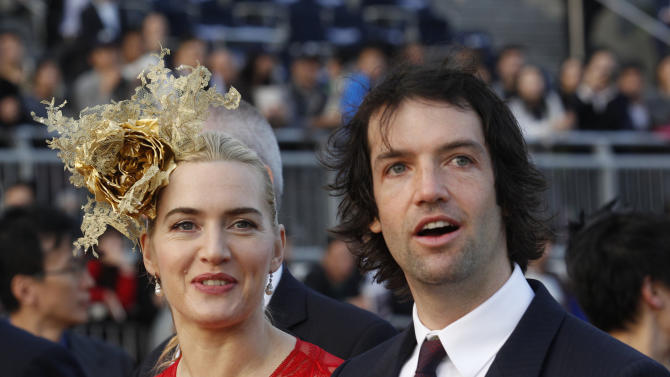 FILE - In this Dec. 9, 2012 file photo, British actress Kate Winslet, left, arrives with Ned Rocknroll at the awards presentation of The Longines Hong Kong Cup horse race at the Shatin race track in Hong Kong. A representative for the 37-year-old Oscar winner confirms Winslet and husband Rocknroll are expecting a child. People.com first reported the pregnancy Tuesday, June 4, 2013. (AP Photo/Kin Cheung, File)