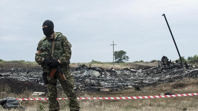 FILE - This July 19, 2014, file photo shows pro-Russian fighter guarding the crash site of Malaysia Airlines Flight 17 near the village of Hrabove, eastern Ukraine. Ukraine said the passenger plane was shot down as it flew over the country, killing all 298 people on board. A series of unanswered questions about the downing of the flight shows the limits of U.S. intelligence-gathering even when it is intensely focused, as it has been in Ukraine since Russia seized Crimea in March. (AP Photo/Evgeniy Maloletka, File)