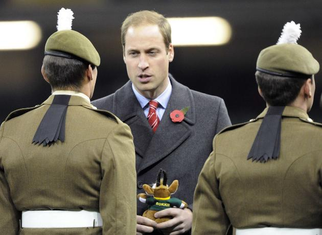 Britain's Prince William holds a South African rugby union soft toy as he talks to soldiers after the international rugby union match between South Africa and Wales at the Millennium Stadium in Cardif