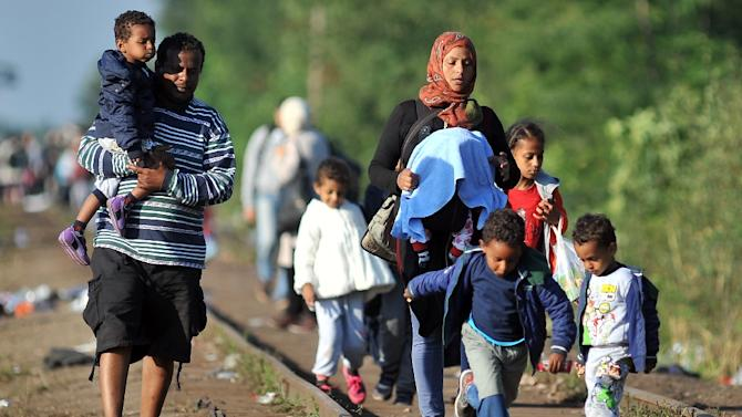 Migrants walk down railway tracks to the Hungarian border near the northern Serbian town of Horgos on September 14, 2015