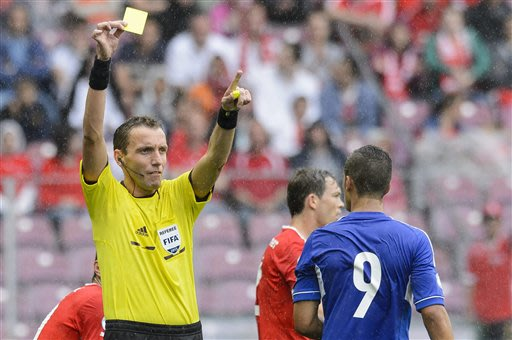 Italian referee Paolo Mazzoleni, left, gives a yellow card to Cyprus' forward Pieros Sotiriou, right, during the 2014 FIFA World Cup group E qualification soccer match between Switzerland and Cyprus a