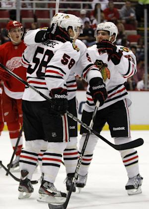Chicago Blackhawks' Byron Froese (58) celebrates his first period goal with teammates Brad Mills and Ben Smith, right, during a preseason NHL hockey game against the Detroit Red Wings Sunday, Sept. 22, 2013 in Detroit. Froese scored two goals in a 4-3 win over the Red Wings. (AP Photo/Duane Burleson)