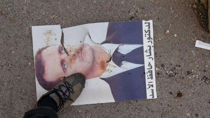 """This citizen journalism image provided by Edlib News Network, ENN, which has been authenticated based on its contents and other AP reporting, shows a Syrian rebel stepping on a portrait of Syrian President Bashar Assad, at Taftanaz air base that was captured by the rebels, in Idlib province, northern Syria, Friday Jan. 11, 2013. Islamic militants seeking to topple President Bashar Assad took full control of a strategic northwestern air base Friday in a significant blow to government forces, seizing helicopters, tanks and multiple rocket launchers, activists said. The Arabic words in the portrait read:""""The doctor Bashar Hafez Assad"""". (AP Photo/Edlib News Network ENN)"""
