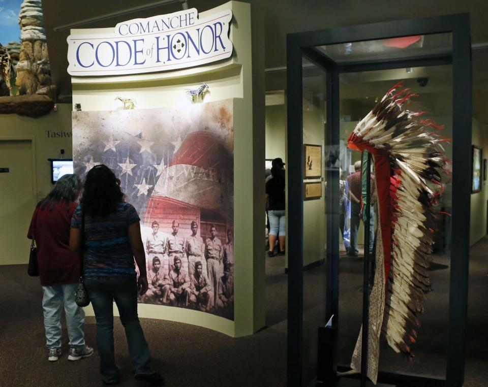 People walk through an exhibit about the Comanche Code Talkers at the Comanche National Museum & Cultural Center in Lawton, Okla, Thursday, Sept. 26, 2013. (AP Photo/Sue Ogrocki)