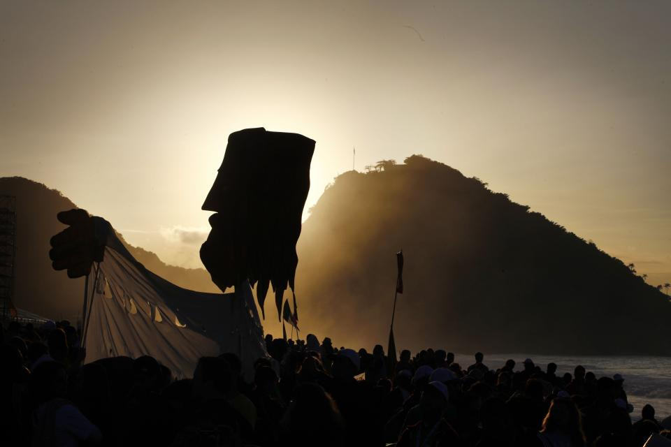 Pilgrims carry a large puppet representing Jesus as the sun raises over Copacabana beach in Rio de Janeiro, Brazil, Sunday, July 28, 2013. Hundreds of thousands of young people slept under chilly skies in the white sand awaiting Pope Francis' final Mass for World (AP Photo/Jorge Saenz)