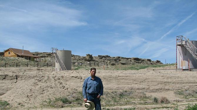 """In this May 22, 2009 photo shows John Fenton, a farmer who lives near the rural community of Pavillion in central Wyoming, outside his log home near a tank used in natural gas extraction. Fenton and some of his neighbors blame hydraulic fracturing, or """"fracking,"""" a common technique used in drilling new oil and gas wells, for fouling their well water and possibly causing health problems among residents. The U.S. Geological Survey plans to release results of the latest testing in the Pavillion area, where some homeowners and the EPA suspect hydraulic fracking has tainted the groundwater. (AP Photo/Bob Moen)"""
