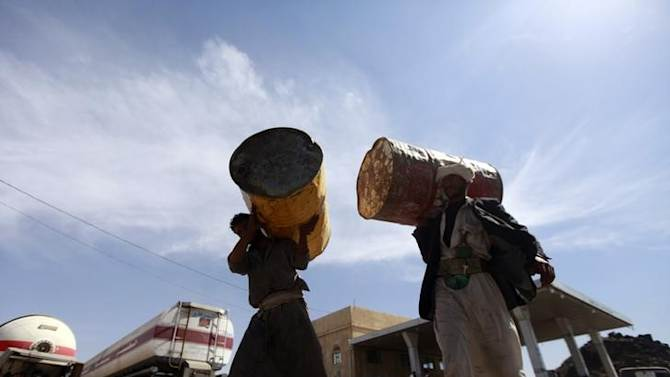 Farmers carry barrels at a fuel station during a diesel shortage in Sanaa