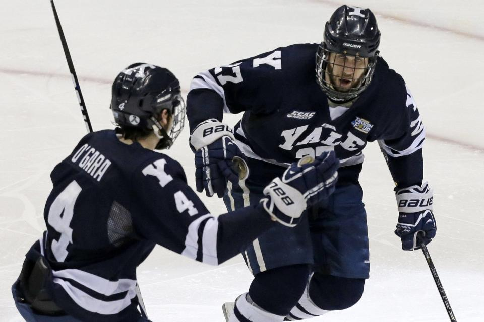 Yale's Charles Orzetti (27) celebrates his third period goal with Rob O'Gara (4) in the NCAA men's college hockey Frozen Four national championship game in Pittsburgh, Saturday, April 13, 2013. Yale defeated Quinnipiac 4-0.  (AP Photo/Gene J. Puskar)