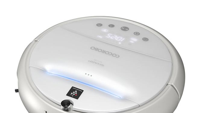 "In this undated image released by Sharp Corp. Cocorobo sold by the Japanese electronics maker is shown. It looks just like iRobot's Roomba vacuuming machine, except the new circular roaming vacuum cleaner from Sharp is trilingual, and even knows a hip humorous dialect. Cocorobo, which can also send photos taken from your home to your cell phone, says 36 phrases including ""Long time no see"" and ""Hello,"" in Japanese, English and Chinese. Cocorobo sells for 130,000 yen ($1,600) and goes on sale next month in Japan, and later in China and other Asian nations.(AP Photo/Sharp Corp.)"