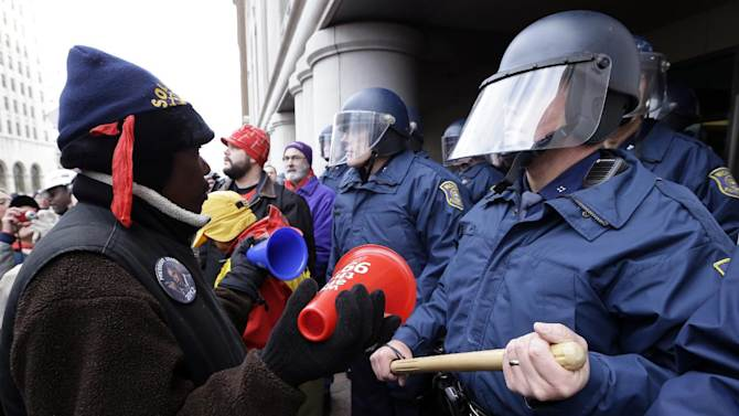 A protester rallies in front of Michigan State Police at the George W. Romney State Building, where Gov. Snyder has an office in Lansing, Mich., Tuesday, Dec. 11, 2012. The crowd is protesting right-to-work legislation passed last week. Michigan could become the 24th state with a right-to-work law next week. Rules required a five-day wait before the House and Senate vote on each other's bills; lawmakers are scheduled to reconvene Tuesday and Gov. Snyder has pledged to sign the bills into law. (AP Photo/Paul Sancya)
