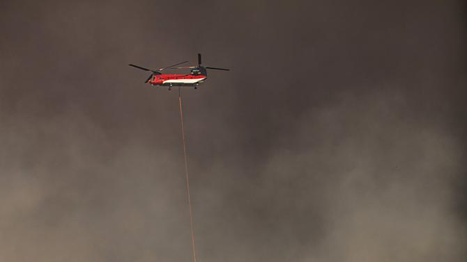 A helicopter drops water to protect a home from the rapidly moving Rocky Fire in Lake County, California