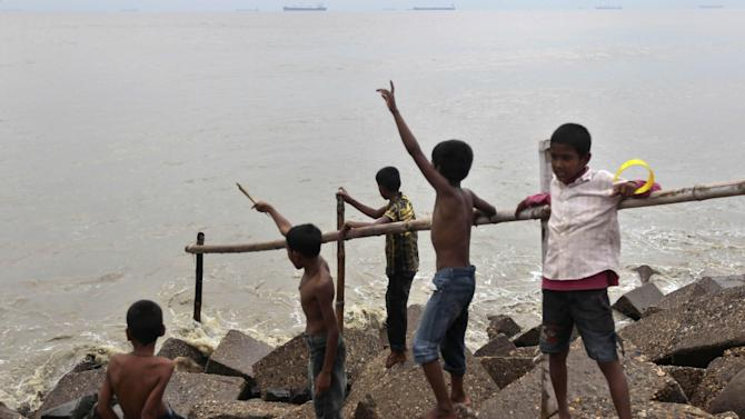 Bangladeshi children play on the banks of the Bay of Bengal sea in Chittagong, Bangladesh, Wednesday, May 15, 2013. People living in coastal areas in Bangladesh and Myanmar are being evacuated as tropical cyclone Mahasen appears to make landfall late Thursday or early Friday, according to news reports. (AP Photo/A.M. Ahad)