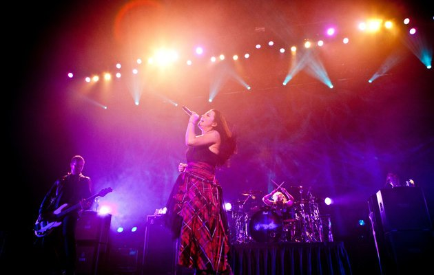Amy Lee belting out a song with her band members in the background. (Photo credit: Marcus Lin)