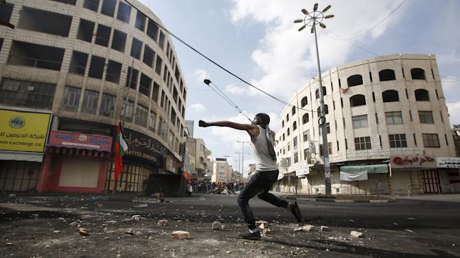 Palestinian uses a slingshot agains Israeli troops during clashes in the West Bank city of Hebron