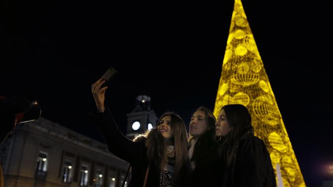 A group of women take a selfie near a Christmas tree made out of lights at Madrid's landmark Puerta del Sol square