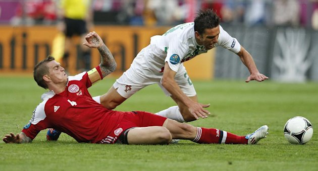 Portugal's Helder Postiga is tackled by Denmark's Daniel Agger, left, during the Euro 2012 soccer championship Group B match between Denmark and Portugal in Lviv, Ukraine, Wednesday, June 13, 2012. (AP Photo/Armando Franca)