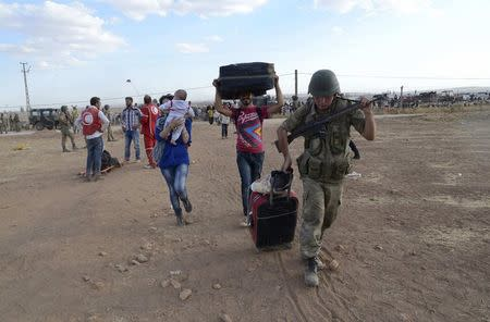 Turkish soldier helps Syrian Kurds with their luggage after they crossed into Turkey, at the Turkish-Syrian border near the southeastern town of Suruc in Sanliurfa province