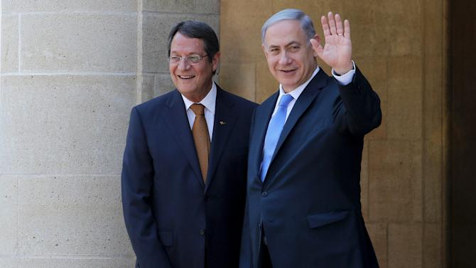 Cyprus' President Anastasiades and Israel's Prime Minister Netanyahu waves to media at the presidential palace in Nicosia