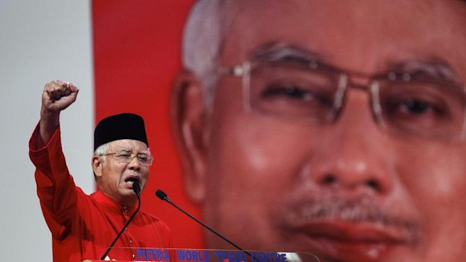 FILE- In this May 11, 2015 file photo, Malaysian Prime Minister Najib Razak addresses delegates during his speech at the Malaysia's ruling party United Malays National Organization's (UMNO) anniversary celebration in Kuala Lumpur, Malaysia. Najib is facing the risk of a criminal charge over allegations that millions of dollars were funneled from an indebted state fund to his personal bank accounts, the first time the country's leader has faced criminal allegations. The attorney general confirmed late Saturday, July 4, 2015 he has received documents from an official investigation that made the link between Najib and the investment fund 1MDB.  (AP Photo/Joshua Paul, File)