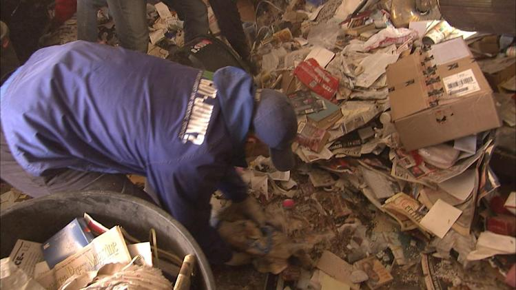"Crew gathering up trash that's compacted on the ground in season premiere of ""Hoarders."""