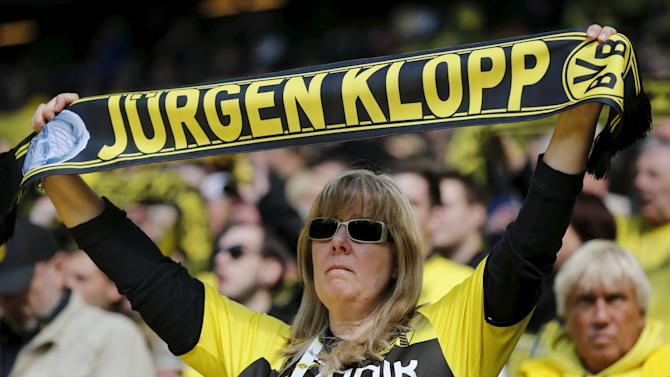 Supporter of Borussia Dortmund holds up a scarf for coach Juergen Klopp before his team's first division Bundesliga soccer match against SC Paderborn in Dortmund