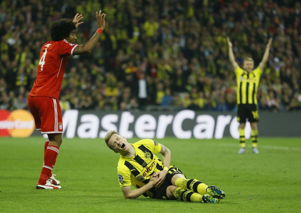 Bayern's Dante of Brazil, left, fouls Dortmund's Marco Reus, leading to a penalty,  during the Champions League Final soccer match between Borussia Dortmund and Bayern Munich at Wembley Stadium in London, Saturday May 25, 2013. (AP Photo/Kirsty Wigglesworth)