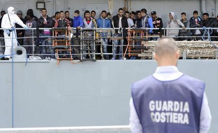 Migrants wait to disembark from the Irish navy ship LÉ Eithne as they arrives in the Sicilian harbour of Palermo