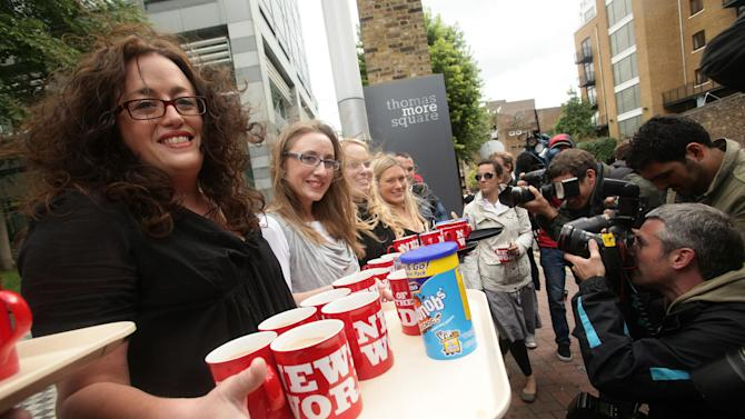 Sub-editors from The News Of The World bring cups of tea for the media outside News International  site in Wapping, east London Saturday July 9, 2011.  The 168-year-old tabloid News of the World was shut down Thursday after being engulfed by allegations its journalists paid police for information and hacked into the phone messages of celebrities, young murder victims and even the grieving families of dead soldiers. Its last publication day is Sunday. (AP Photo/Yui Mok/PA)