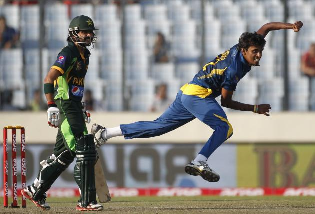 Sri Lanka's Suranga Lakmal bowls as Pakistan's Fawad Alam watches during their 2014 Asia Cup final match in Dhaka