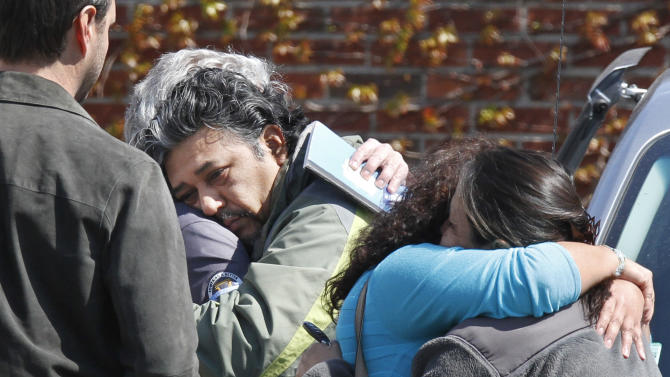 Jose Garcia, center, is consoled after the body of his missing son, Boston College student Franco Garcia, was recovered at Chestnut Hill Reservoir in Boston, Wednesday, April 11, 2012.  Franco Garcia disappeared Feb. 22 after leaving a popular bar near the college. (AP Photo/Michael Dwyer)