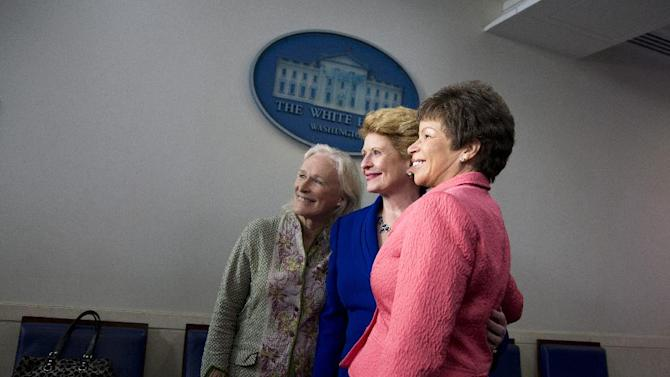 From left, actress Glenn Close, Sen. Debbie Stabenow, D-Mich., and White House adviser Valerie Jarrett pose for photographs in the White House briefing room in Washington, Monday, June 3, 2013, after doing a television interview ahead of the White House mental health conference with President Barack Obama. The conference was organized as part of President Obama's response to last year's shooting massacre at a Connecticut elementary school. (AP Photo/Evan Vucci)