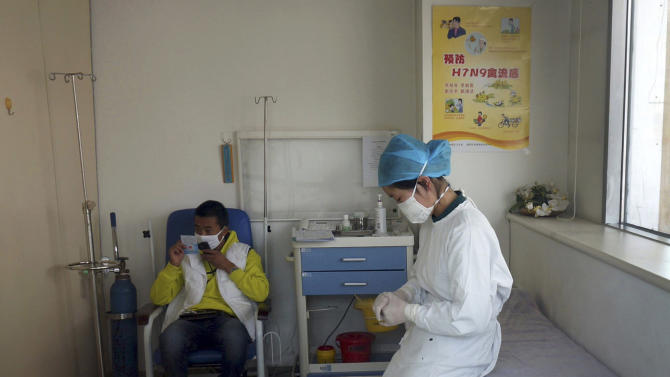A nurse stays with a patient at a specialized fever clinic inside the Ditan Hospital, where a Chinese girl warded for the H7N9 strain of bird flu, in Beijing Saturday, April 13, 2013. The 7-year-old girl has become the first confirmed case in Beijing of the latest strain of bird flu virus, which has killed 11 and sickened 34 others in eastern China, officials said Saturday. (AP Photo) CHINA OUT