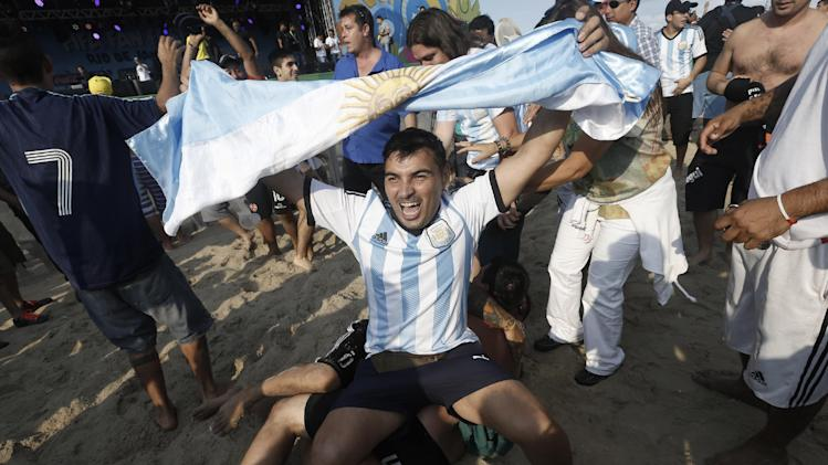 Argentina soccer fans celebrates their team's victory over Iran after a live telecast of the World Cup match inside the FIFA Fan Fest area on Copacabana beach, in Rio de Janeiro, Brazil, Saturday, June 21, 2014. Argentina won 1-0