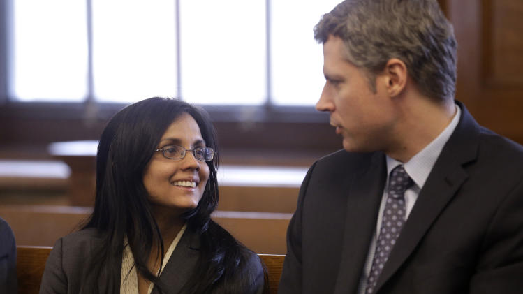 Annie Dookhan, left, a former Massachusetts chemist accused of faking test results at a state drug lab, speaks with her lawyer Nick Gordon, right, moments before her arraignment at Norfolk Superior Court, in Dedham, Mass., Wednesday, Jan. 9, 2013. Prosecutors allege Dookhan fabricated test results and tampered with drug evidence while testing substances in criminal cases.  (AP Photo/Steven Senne, Pool)