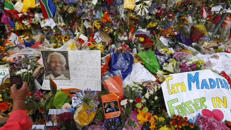A woman takes photos of flowers outside the house where former South African President Nelson Mandela died, in Johannesburg