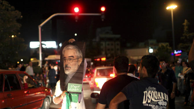 A supporter of Iranian presidential candidate Hasan Rowhani holds up a poster of Green Movement leader Mir Hossein Mousavi, who was a candidate in 2009 and is currently under house arrest, while celebrating Rowhani's victory, in Tehran, Iran, Saturday, June 15, 2013. Wild celebrations broke out on Tehran streets that were battlefields four years ago as reformist-backed Rowhani capped a stunning surge to claim Iran's presidency on Saturday, throwing open the political order after relentless crackdowns by hard-liners to consolidate and safeguard their grip on power. (AP Photo/Ebrahim Noroozi)