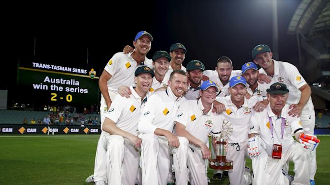 Australia's captain Steve Smith holds the Trans Tasman trophy as he celebrates with his team mates after they defeated New Zealand in the third cricket test match and the series at the Adelaide Oval, in South Australia