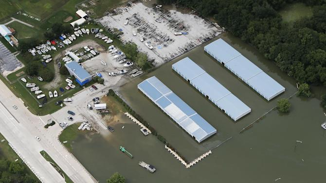 A covered dry boat storage complex is inundated with flood waters at the Joe Pool Lake marina, Friday, May 29, 2015, in Grand Prairie, Texas. Floodwaters submerged Texas highways and threatened more homes Friday after another round of heavy rain added to the damage inflicted by storms. (AP Photo/Brandon Wade)