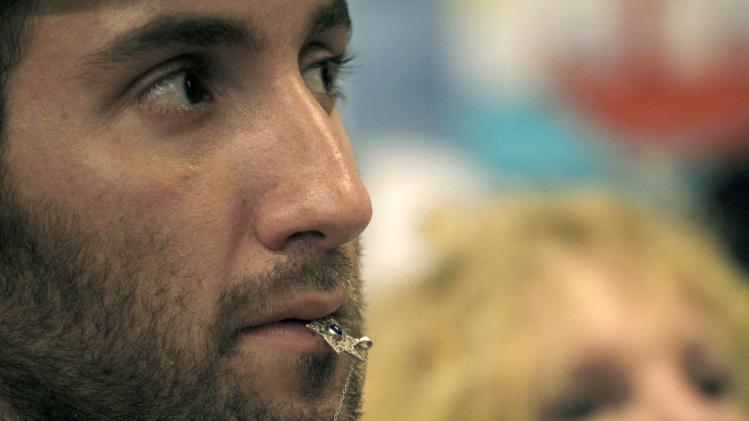 Human rights activist Gabriel Matthew Schivone, from Tucson, Ariz., holds in his lips a star of David as he attends a news conference about an international flotilla to blockaded Gaza, in Athens, Monday, June 27, 2011. Organizers say Israel is pressuring Greece to halt the ships' departure.(AP Photo/Petros Giannakouris)