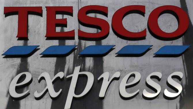 The Houses of Parliament are reflected in a Tesco sign in central London