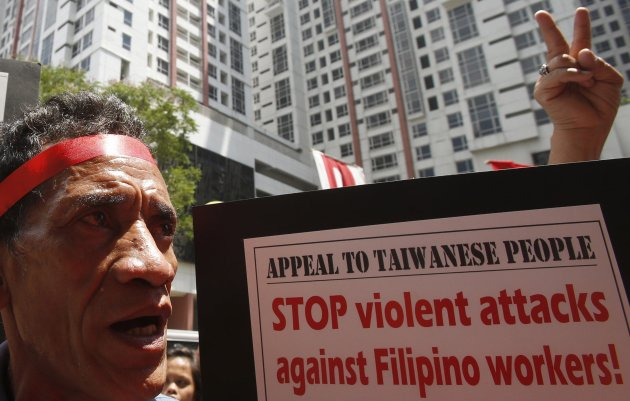 An overseas Filipino worker chants slogans during a rally outside the premises of the Taipei Economic and Cultural Office (TECO), in Manila's Makati financial district