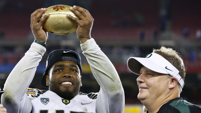 FILE - In this Jan. 3, 2013 file photo, Oregon's Michael Clay, left, holds up the championship trophy as head coach Chip Kelly looks on after the Fiesta Bowl NCAA college football game against Kansas State in Glendale, Ariz. The Philadelphia Eagles have hired Kelly after he originally chose to stay at Oregon. Kelly becomes the 21st coach in team history and replaces Andy Reid, who was fired on Dec. 31 after a 4-12 season. (AP Photo/Ross D. Franklin, File)