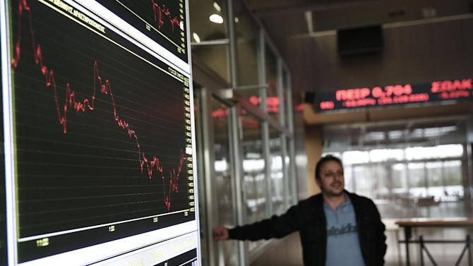 An employee of the Stock Exchange stands next to a board showing share prices in Athens, on Tuesday, Jan. 27, 2015. A radical left-wing party vowing to end Greece's painful austerity program won a historic victory in Sunday's parliamentary elections, setting up a showdown with the country's international creditors that could shake the eurozone. Greek stocks tumbled more than 5 percent Tuesday, before recouping some losses to close the day 3.7 percent down, on the back of a 3.2 percent loss Monday. (AP Photo/Petros Giannakouris)